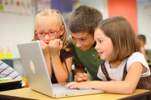 Elementary school students look at laptop computer